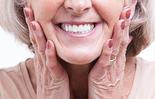 Senior woman showing her dentures with a smile