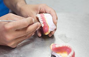 Dental Technician Fixing Dentures
