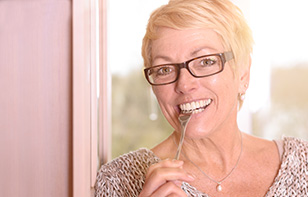 Happy Blonde Woman Biting a Fork While Showing Her New Dentures