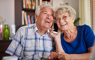 A Very Old Couple Smiling When Talking To Loved Ones Over Phone